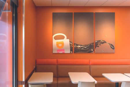 GoCo Dunkin Donuts dining area with coffee art on the wall